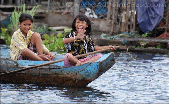 Small kids in charge of boat but finding time to wave at tourists
