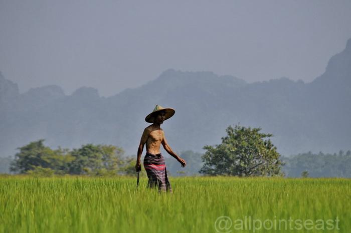 Karen farmer with Zhwegabin Mountain behind