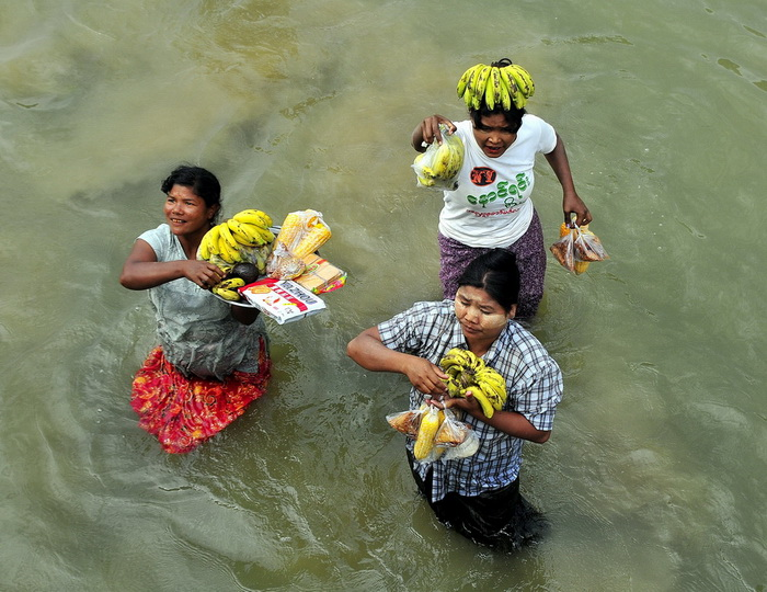 Banana vendors sell their wares to a tour boat