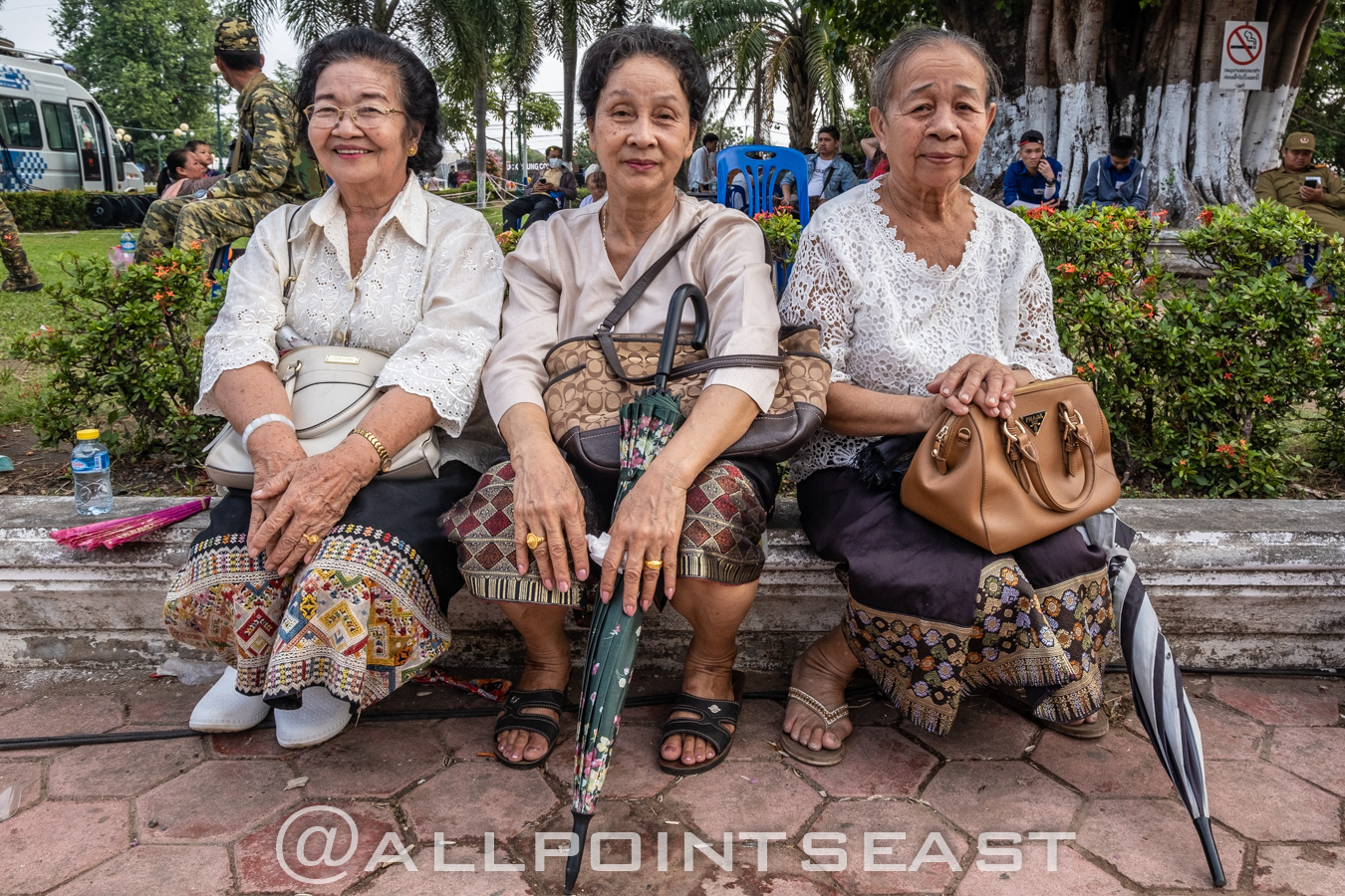 Lao matriachs hanging out in the park with traditional-style sarongs. by Jeff Pergiois